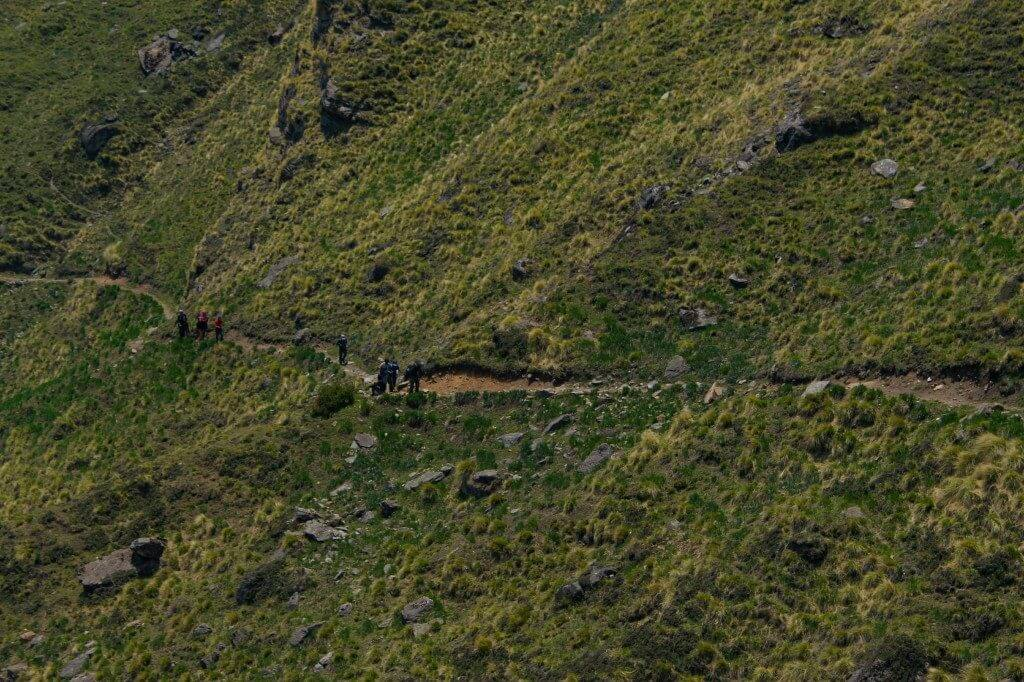 Trekkers approaching the Gorson Bugyal through a narrow trail - Pangarchulla Peak